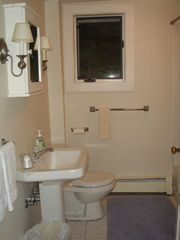 Dorset house photo - Simple first floor bathroom, shower over tub and shelving to right.