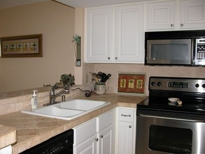 Kitchen area has new appliances, tumbled marbled tops & backsplash.