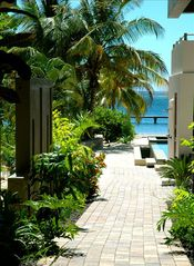 Beautiful walkways with lush tropical flowers - Roatan hotel vacation rental photo