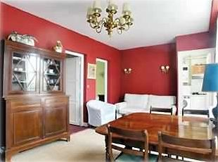 Vast living room/dining room with antique furniture & a comfortable sofa bed.