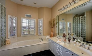 Master bathroom of Master Suite 1 with double sinks and a Jacuzzi tub.