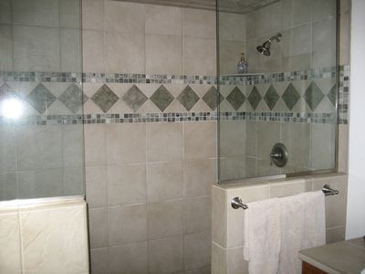 This bathroom has 2 showers, heated tile floors.