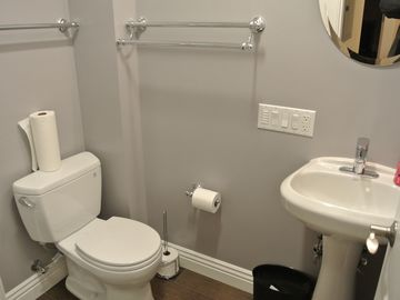 Bathroom 2 with pedestal sink and ample towel racks and hook.