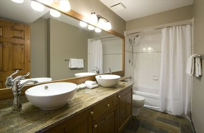 Two above counter sinks sit on beautiful granite vanity top.