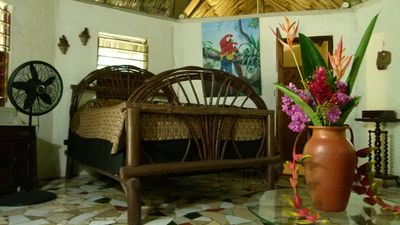 Interior of Macaw Cabana with queen size bed, private hot and cold shower