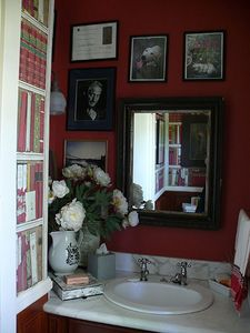 Powder room. Brunschwig & Fils library wall paper and personal memorabilia.