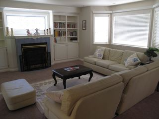 Bright living room with leather sofa set, gas fireplace and book collection - Montgomery Estates house vacation rental photo