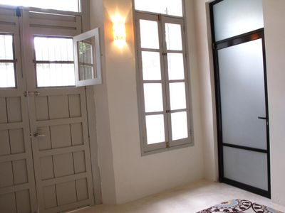 Second bedroom looking out to courtyard through double door and window.