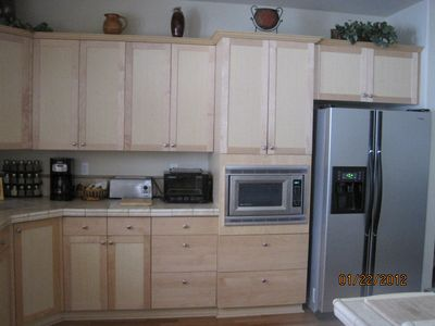 Kitchen area with dual fuel range with gas stove top and electric oven.