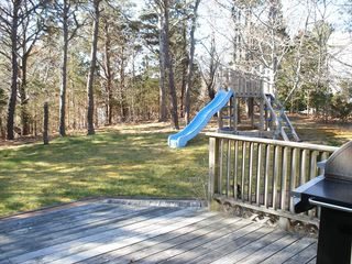 Eastham house photo - Kid friendly back yard has a play-set with slide and room to run.