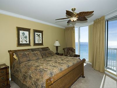 Master Bedroom which opens to large patio with view of pools, white-sand beach.