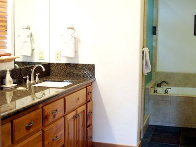 Master bath w/ his n her sinks, natural stone floors, soak tub & walk-in shower.