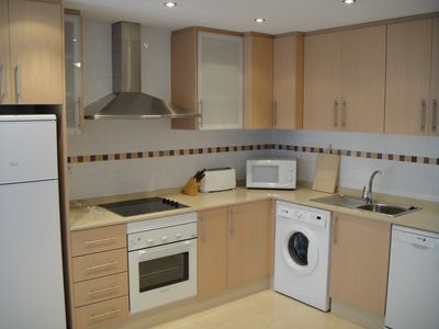 Kitchen with dishwasher, oven, hob, microwave, fridge freezer, washing machine.