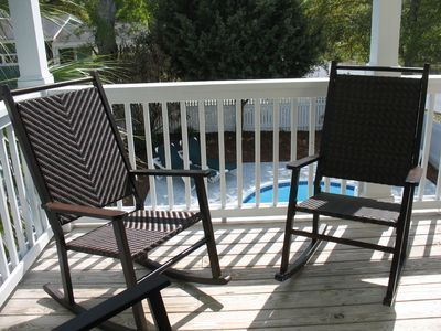 Large covered deck off main living area also has a table, direct access to pool.