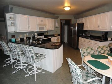 Up-dated kitchen with lots of seating. Plenty of dishes,.glasses,utensils,etc.