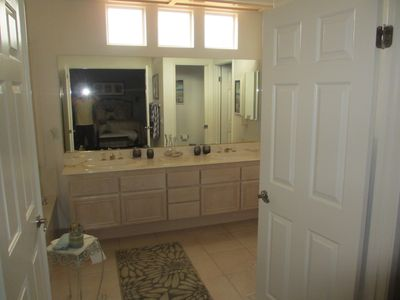 Master bath with Jacuzzi tub, shower, two sinks, and walk in closet