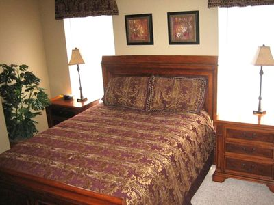 Guest bedroom with queen bed and TV