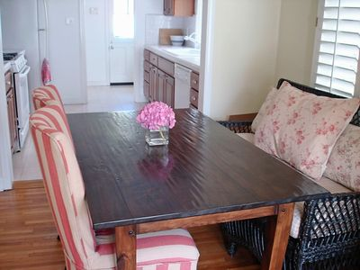 Dining room; great farm table and wicker settee; galley kitchen