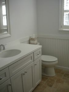 Main bathroom with travertine floors and tub.