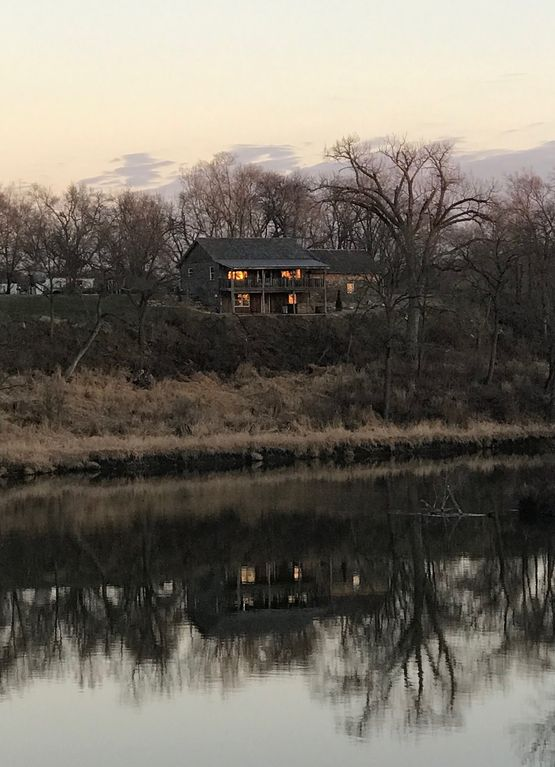 Cabin on bluff of Big Sioux River with rushing waters of the Klondike Dam below.