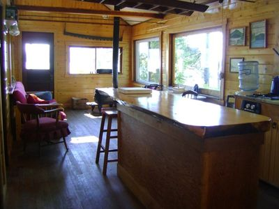 Pine slab kitchen bar and living room. Woodstove in far right corner.