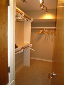 Large, walk-in closet in master suite with hangers and shelving provided