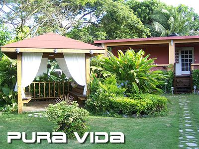 Pura Vida as seen from road. Large gazebo with benches and hammock.