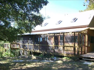Screened-in front porch with b-b-q pit and view of the Pedernales River