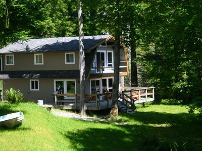 Exterior view of the cabin. Shows private balcony off larger top floor room.