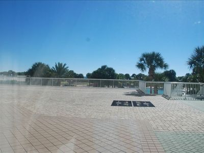 Walk out to the Large patio area just outside the unit., & down to the pool,