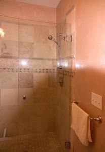 large walk-in, tiled shower with glass door