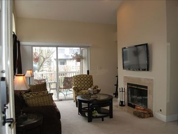 Large, comfortable living room with fireplace, flat screeen TV, opens to patio.