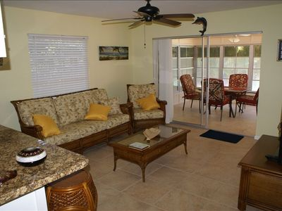 "Living room with 42"" Sat TV and ""Tommy Bahama"" furniture. extends into lanai."