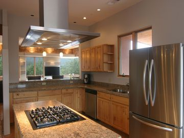 Kitchen with gas range, double ovens, wine cooler, wet bar, window seat