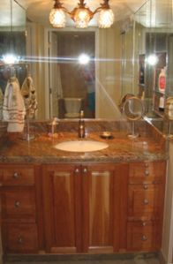 Mirrored vanity area with pineapple fixture, granite and cherrywood