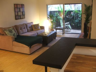 Den area with bamboo floors, flat screen tv, sectional couch, patio view.