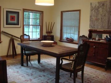 Open dining room overlooking front lawn and woods.