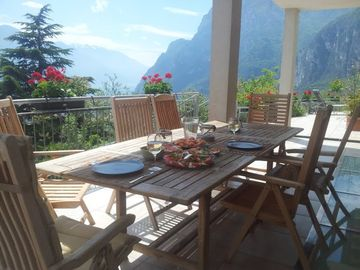 Al fresco dining under covered patio overlooking lago di Garda, Riva & Dolomiti.