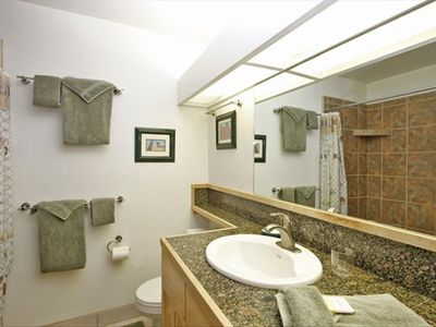 Large walk-in shower and granite counters in the bathroom.