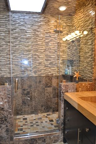 Walk-in sky lit spa shower with bench and intricate tile work.