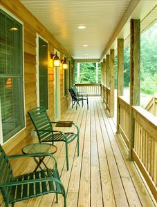 Relaxing front porch looks over lawn and woods.