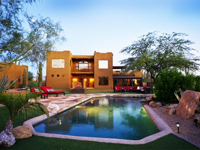 Scottsdale house rental - breathtaking view of backyard and the back of the house during dusk.