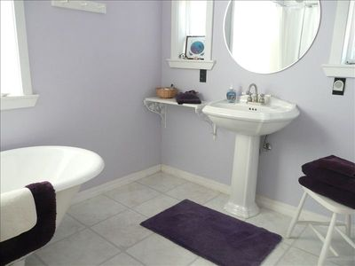 The master bath has a relaxing  claw-foot tub/shower and pedestal sink.