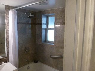Queens studio photo - Granite encased whirlpool tub/shower area