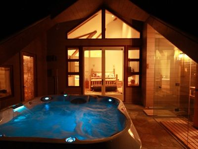 Hot tub and outdoor glass-enclosed sauna off master suite