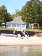 Port Sanilac cottage photo - View of cottage from sand bar !! Fire pit on beach, row boat,chairs & umbrel