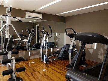 Gym on 10th floor with treadmill, bike, elliptical machine, dumbbells and machin