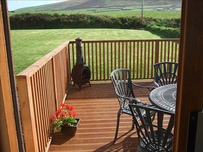 Deck off kitchen/Dining room. Overlooks back lawn, fields, mountain & ocean.