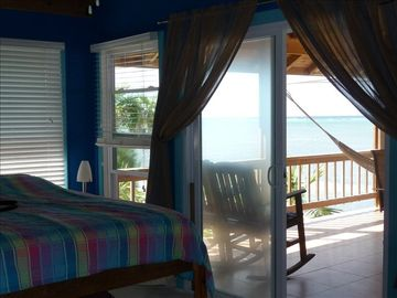Sapphire blue bedroom adjacent to large deck overlooking the beach and sea