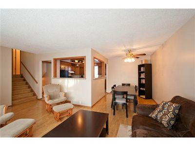 Calgary house rental - view of living room into dining room, kitchen & stairs leading to 3 bd 1.5 baths